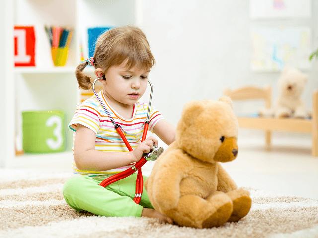 Dieťa hrajúce sa na doktora s plyšákom