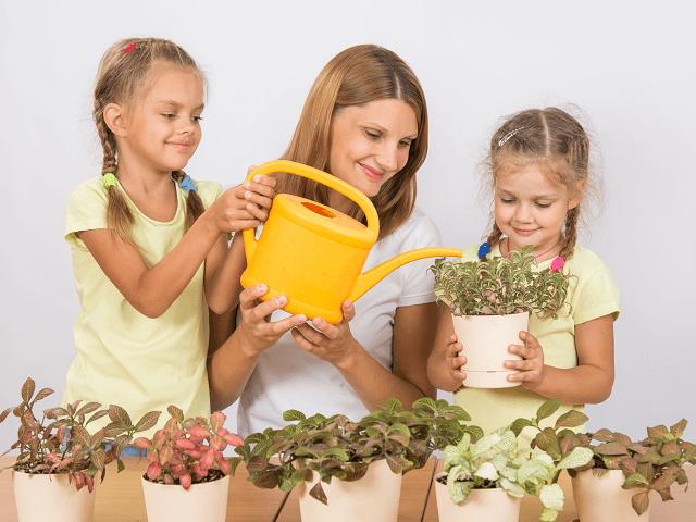 Matka s deťmi polieva kvety