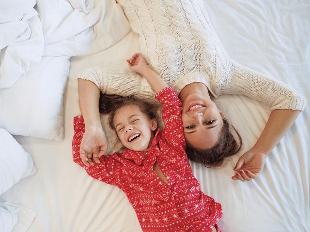 Dcéra a matka ležia vedľa seba na posteli a relaxujú